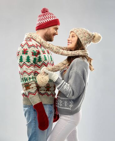 christmas, winter clothes and holidays concept - portrait of happy couple at ugly sweater party Stockfoto