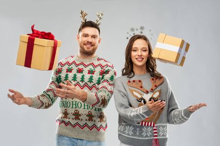 people and holidays concept - portrait of happy couple with christmas gifts at ugly sweater party