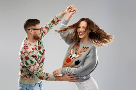 celebration, fun and holidays concept - happy couple wearing ugly sweaters dancing at christmas party Stockfoto