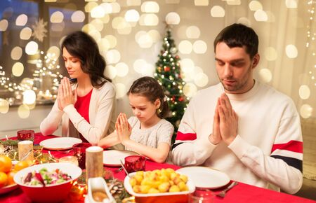 holidays, family and celebration concept - happy mother, father and little daughter having christmas dinner and praying before meal at home