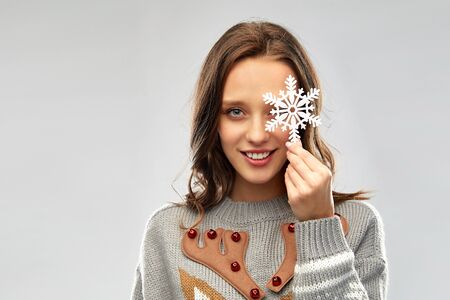 christmas, people and holidays concept - happy young woman with snowflake decoration wearing ugly sweater Stockfoto - 129873580