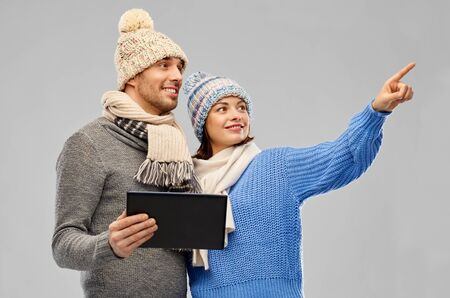 technology, christmas and winter clothes concept - happy couple in knitted hats and scarves with tablet computer over grey background