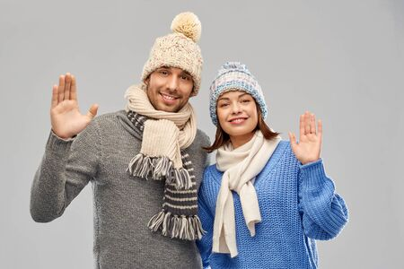 people, christmas and winter clothes concept - happy couple in knitted hats and scarves waving hands over grey background