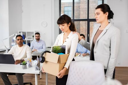 business, firing and job loss concept - colleague seeing off sad fired asian female office worker holding box of his personal stuff
