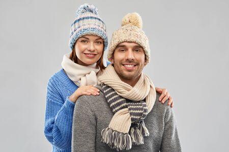 personnes, concept de vêtements de noël et d'hiver - couple heureux en bonnets et écharpes tricotés sur fond gris Banque d'images