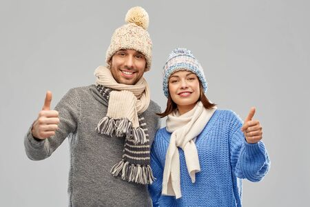 people, christmas and winter clothes concept - happy couple in knitted hats and scarves showing thumbs up over grey background Stockfoto