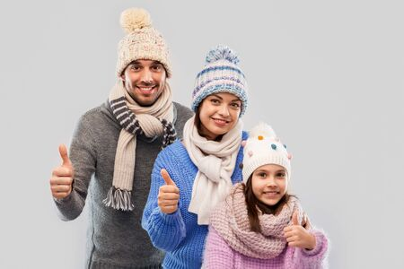 family, christmas and winter clothes concept - happy mother, father and little daughter in knitted hats and scarves showing thumbs up over grey background
