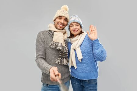 people, christmas and winter clothes concept - happy couple in knitted hats and scarves taking picture by selfie stick over grey background
