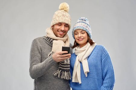 technology, christmas and winter clothes concept - happy couple in knitted hats and scarves with smartphone over grey background