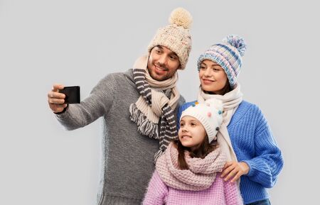 family, christmas and technology concept - happy mother, father and little daughter in winter clothes taking selfie by smartphone over grey background