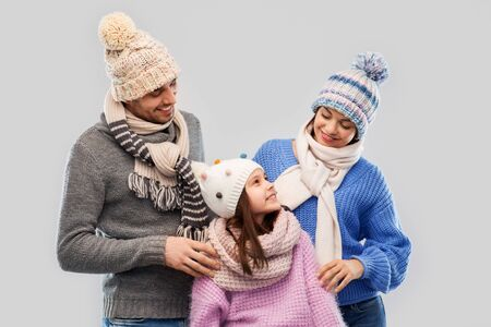 family, christmas and winter clothes concept - happy mother, father and little daughter in knitted hats and scarves over grey background Stockfoto
