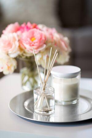 concept de décoration, hygge et confort - diffuseur de roseaux aromatiques, bougie et bouquet de fleurs sur table en bois