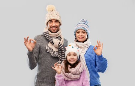 happy family in winter clothes showing ok gesture
