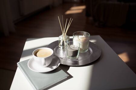 hygge and aromatherapy concept - coffee, candles, book and aroma reed diffuser on table at home