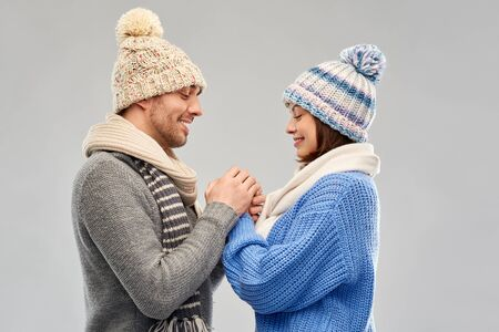 happy couple in winter clothes holding hands