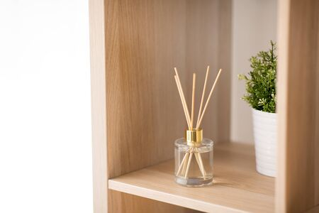 aroma reed diffuser on wooden shelf