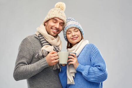 happy couple in winter clothes with mugs Stockfoto - 129938842