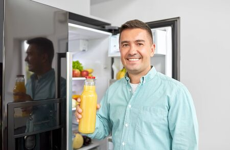 man taking juice from fridge at home kitchen 写真素材