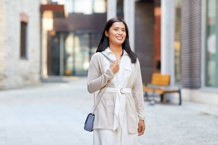 happy smiling young asian woman on city street Stock Photo