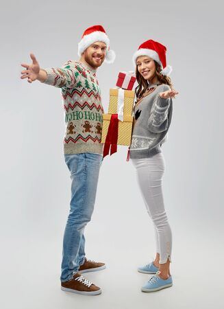happy couple in christmas sweaters with gifts Stockfoto - 129925608