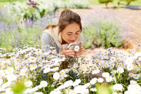 happy woman smelling chamomile flowers in garden