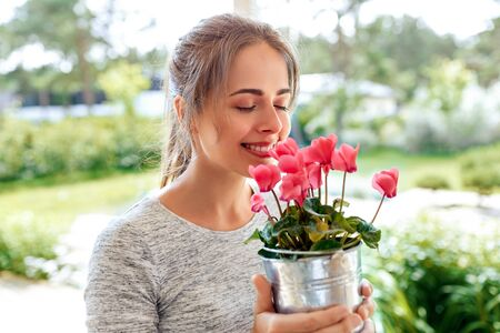 young woman with cyclamen flowers at summer garden