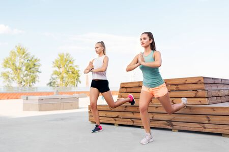 women training and doing split squats Stock Photo
