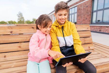 Kinder mit Tablet-Computer sitzen auf Bank