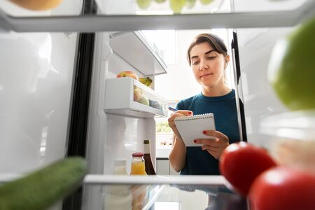 woman making list of necessary food at home fridge Foto de archivo - 129938978