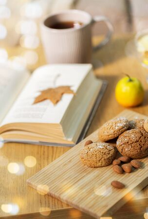 hygge, bake and food concept - oatmeal cookies, almonds, book and tea on wooden table at home Stock Photo