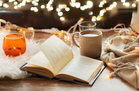 hygge and cozy home concept - book, cup of coffee or hot chocolate and candles with garland on window sill
