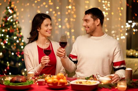 holidays, family and celebration concept - happy couple having christmas dinner at home and drinking red wine Stok Fotoğraf