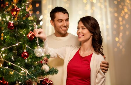 winter holidays and people concept - happy couple decorating christmas tree at home Stok Fotoğraf