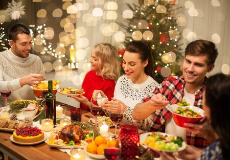 holidays and celebration concept - happy friends having christmas dinner at home and eating food Stock Photo