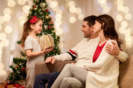 holidays, family and celebration concept - happy mother, father and little daughter with christmas present at home Stok Fotoğraf