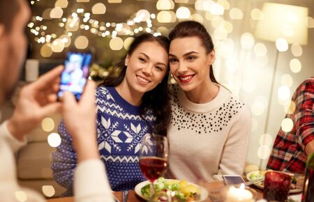 holidays and celebration concept - happy friends having christmas dinner at home and taking picture by smartphone Stock Photo