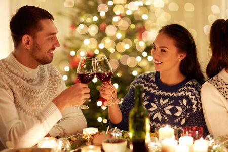 winter holidays and people concept - happy couple celebrating christmas at home feast and drinking red wine