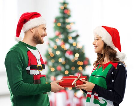 winter holidays, celebration and people concept - happy couple in santa hats and ugly sweaters with gift box at home over christmas tree lights background