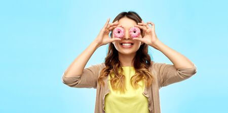 people, fast food and fun concept - happy asian young woman with donuts instead of eyes over blue background Stock Photo