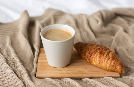 food, eating and breakfast concept - cup of coffee and croissant on bed or blanket at cozy home Фото со стока