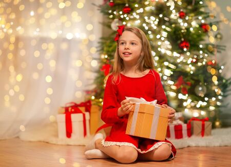 christmas, holidays and childhood concept - smiling girl in red dress with gift box at home Stock Photo