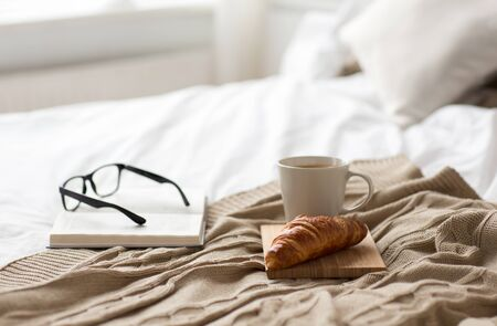 comfort, hygge and interior concept - coffee, croissant, blanket and book on bed at cozy home