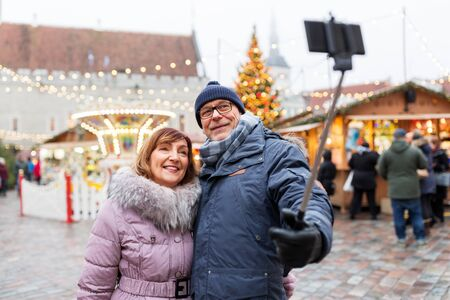 technology, winter holidays and people concept - happy senior couple taking picture by smartphone on selfie stick at christmas market on town hall square in tallinn, estonia