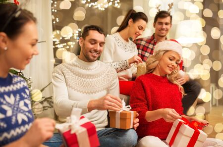 celebration and holidays concept - happy friends with glasses celebrating christmas at home party and opening presents