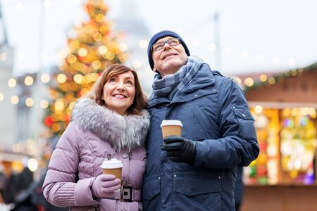 love, winter holidays and people concept - happy senior couple with takeaway coffee at christmas market on town hall square in tallinn, estonia