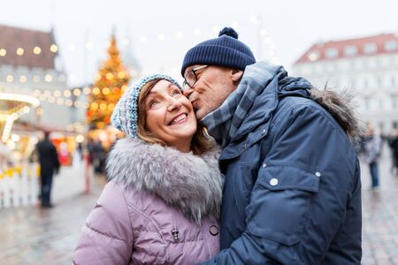 love, winter holidays and people concept - happy senior couple kissing at christmas market on town hall square in tallinn, estonia