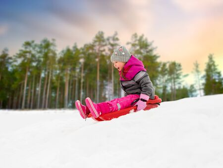 childhood, sledging and season concept - happy little girl sliding down on sled outdoors over winter forest background
