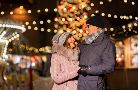 love, winter holidays and people concept - happy senior couple hugging at christmas market on town hall square in tallinn, estonia