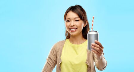 drinks and people concept - happy young asian woman drinking soda from can with paper straw over blue background