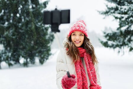 christmas, season and people concept - happy smiling teenage girl or woman taking picture by selfie stick in winter park 写真素材
